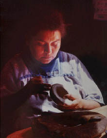 Phoro of Hopi Mesa Native American Potter working in her home, photo copyrighted 2005, all rights reserved.